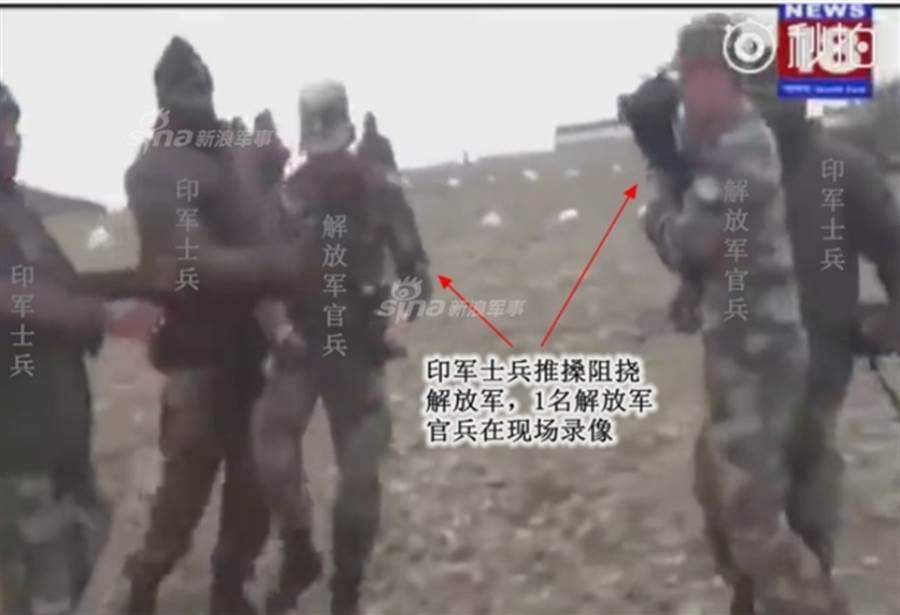 印度士兵在推搡阻撓解放軍,1名解放軍官兵則在現場錄影。(新浪軍事/印度電視台視頻截圖)
