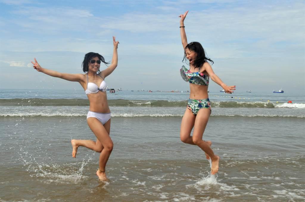 穿著清涼比基尼的泳客,成為海灘上的亮點。(李金生攝)