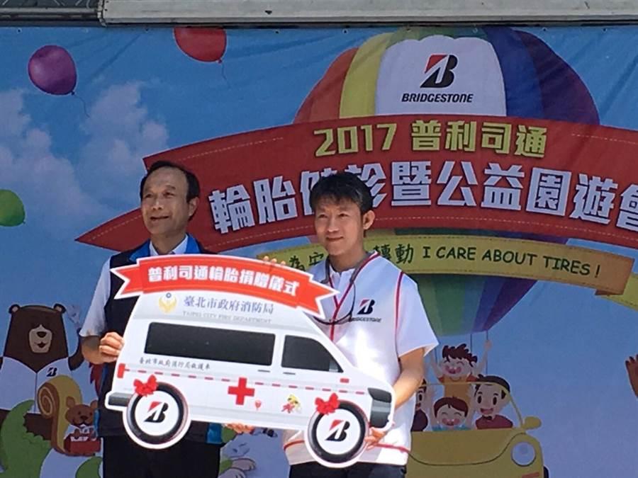北市消防局主任祕書畢幼明(左),代表接受輪胎公司的捐贈。(消防局提供)