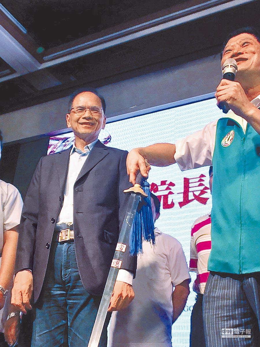 行政院前院長游錫堃(左)22日晚上出席在新北市社會扶助協會活動,市議員陳啟能送上一把貼有「當選」的長劍,力挺游錫堃再戰新北。(陳心瑜攝)
