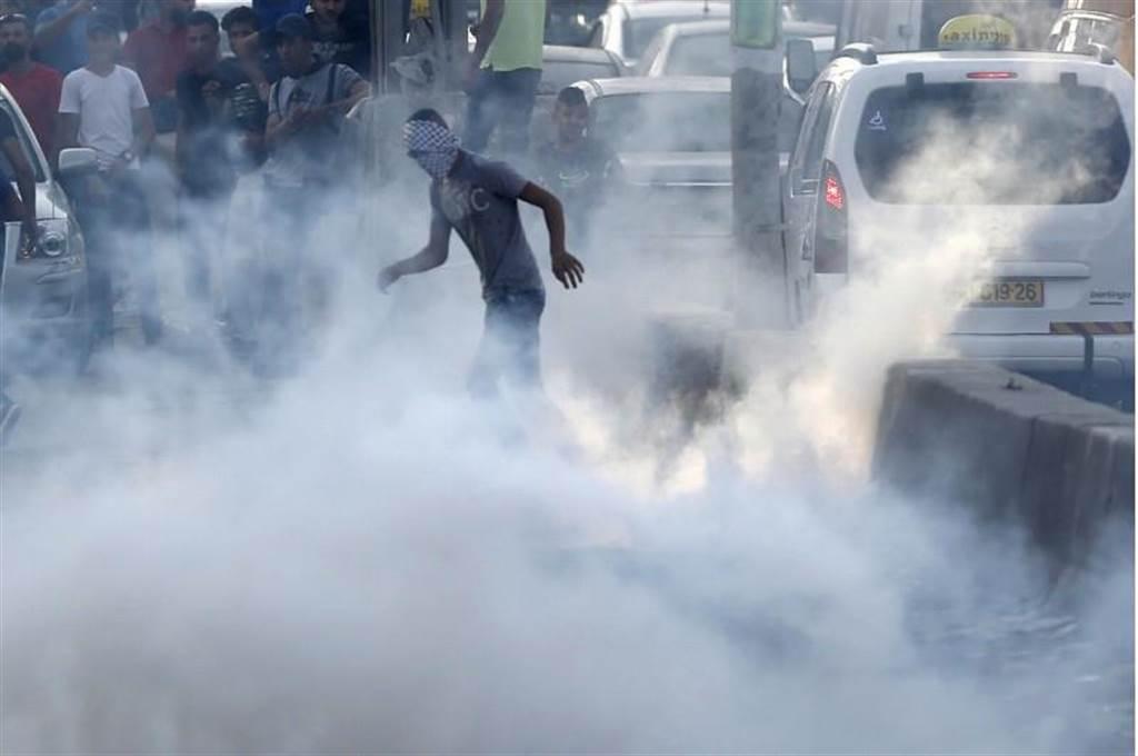 穆斯林聖地耶路撒冷爆發激烈街頭衝突,一名巴勒斯坦民眾在催淚瓦斯中蹣跚前行。(圖/美聯社)