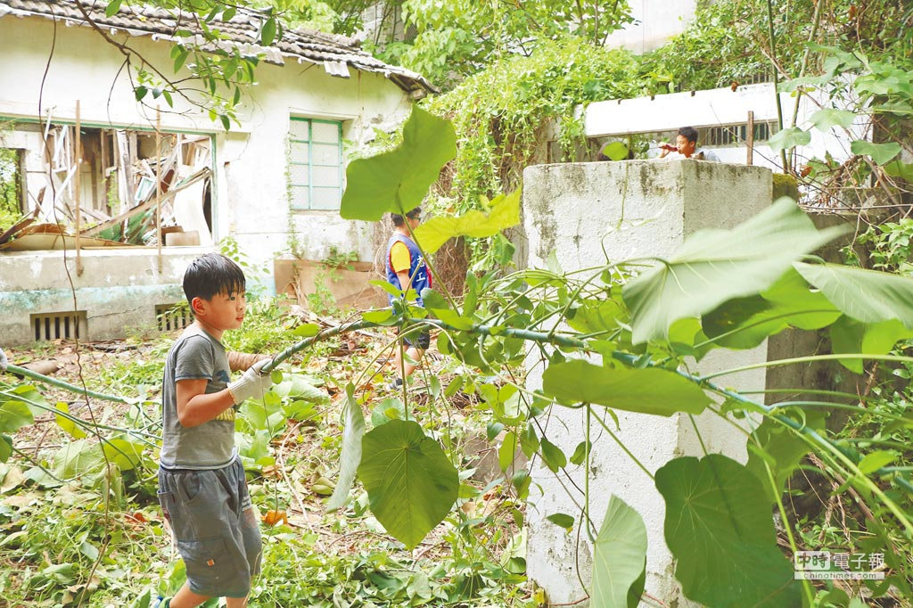 東港共和新村自救會怨軍方不打掃,他們只好自救,大手拉小手自力打掃空置眷舍。  (謝佳潾攝)