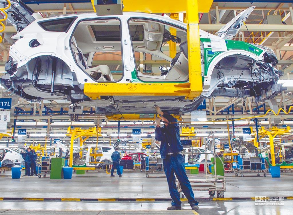 2014年3月31日,長安福特工作人員在重慶工廠安裝車輛底盤零件。(新華社)