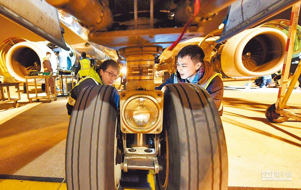 1月19日,南航定檢工廠的工程技術人員在檢修一架波音737飛機起落架。(新華社)