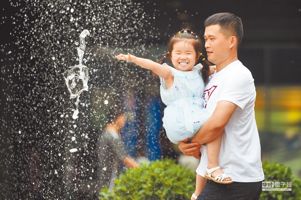 7月12日,一名家長抱著小朋友在北京三里屯的一處噴泉戲水納涼。(新華社)