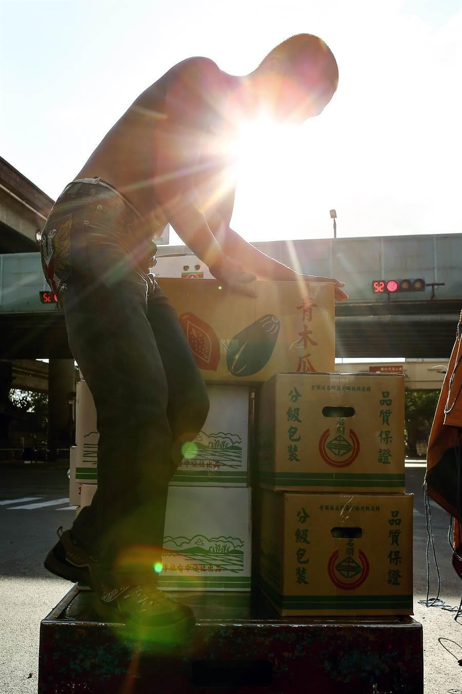 受到尼莎颱風影響,28日傍晚果菜市場內,出現進貨潮,工人在烈日下忙得不可開交。(鄧博仁攝)