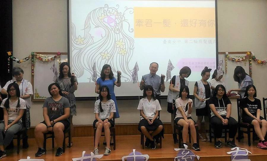 台南女中再辦捐髮活動,這次連校外民眾也來參與,台南女中校長鄭文儀(後排左五)為女同學操刀落髮。(台南女中提供)