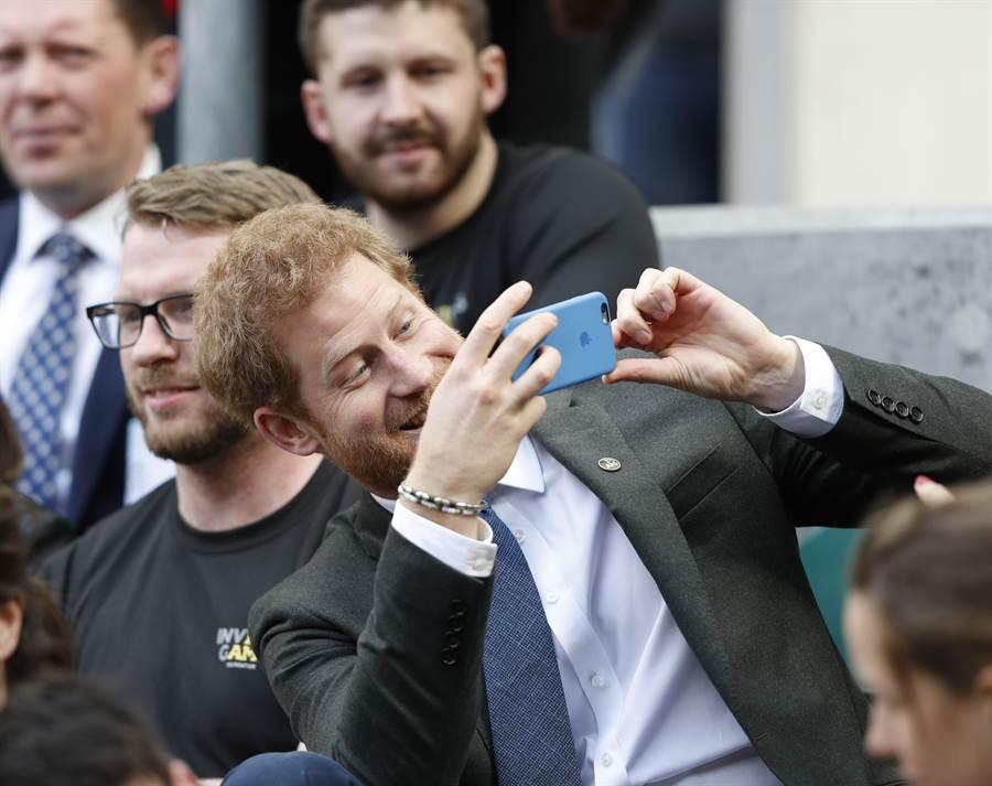 哈利王子4月29日在西倫敦觀看年度陸軍與海軍武裝部隊舉行的英式橄欖球比賽時,拿起手機拍照的神情。(圖/美聯社)