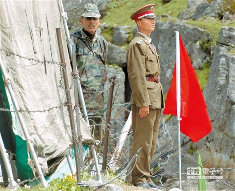 在中印邊境乃堆拉山口,一名中國邊防軍人(右)與一名印度邊防軍人隔著邊界鐵絲網值勤。(資料照片,新華社)
