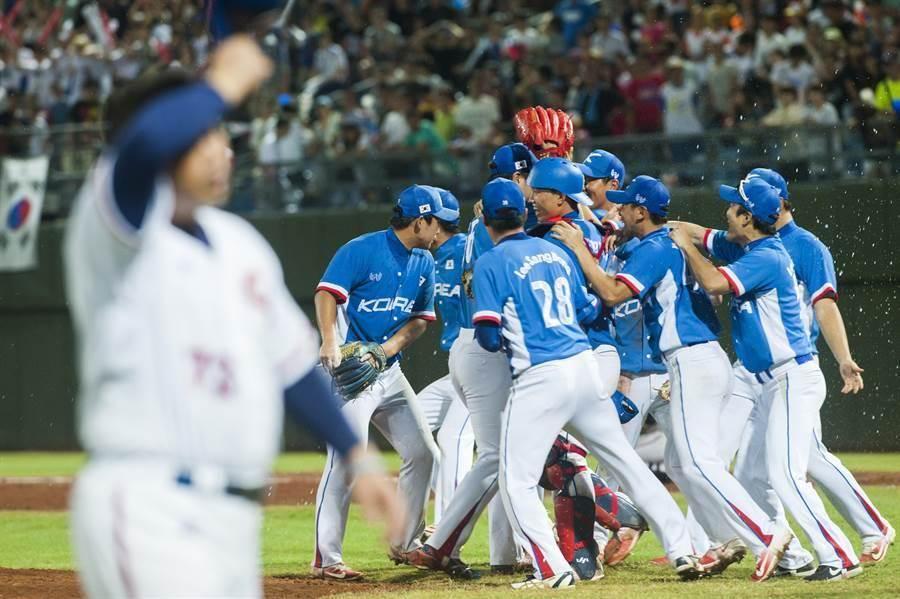 台北世大運棒球比賽23日中韓之戰,中華隊終場以3:6落敗,沮喪的球員走過互相擁抱的韓國球員前。(鄭任南攝)