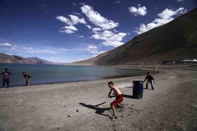 孩童在班公湖岸邊玩板球。(美聯社)