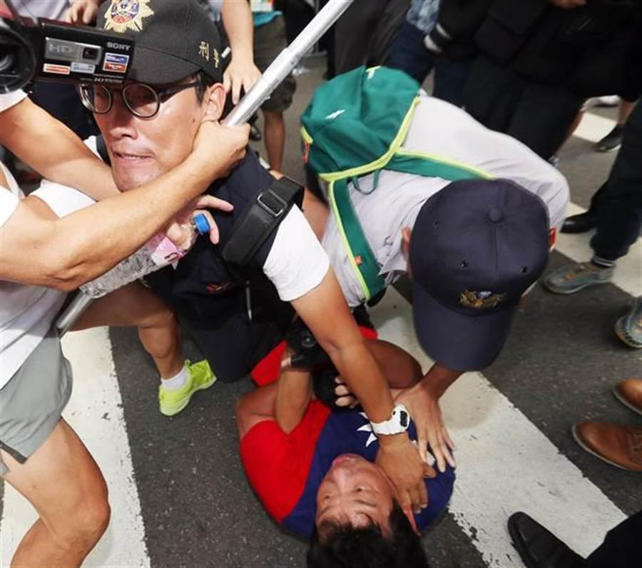 楊思聖強勾北投分局長呂新財脖子,遭當場壓制在地。(陳怡誠攝)