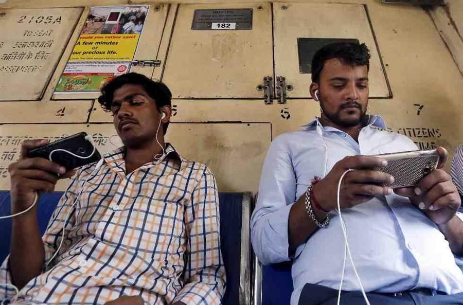 印度孟買火車上的人在通勤時用手機看影片。(美聯社)