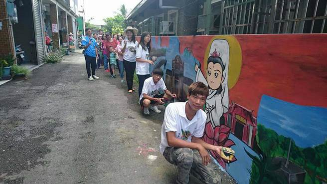 旗山民宿業者以打工換宿方式,讓大學生彩繪社區髒亂牆面做公益。(林雅惠攝)