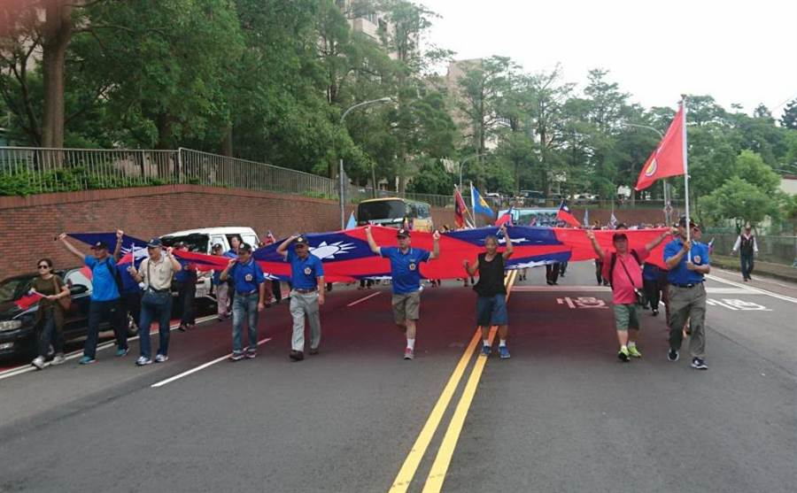 桃園的近400名退伍軍人在九三軍人節,將9面國旗拼成一整面大旗,從虎頭山下忠義公園,遊行到桃園市忠烈祠,堅持年金不該溯及既往。(蔡依珍攝)