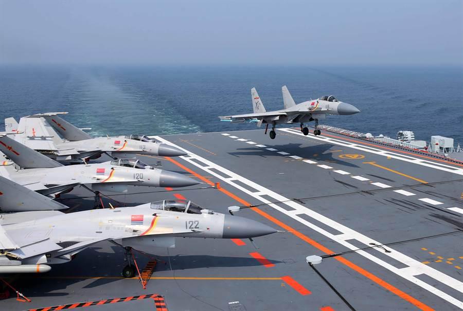 分析認為,遼寧艦艦載機應該在今年7月訪問香港前就已滿編,圖為中國「遼寧」艦編隊抵港,參加香港回歸暨解放軍進駐香港20周年慶祝活動期間,殲-15艦載戰機在艦上阻攔著艦的畫面。(圖/中新社)。