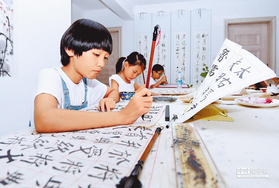 大陸教育部將書法納入中小學課程,讓學生臨摹名家書法,體會古詩、文言文與漢字之美。(新華社提供)