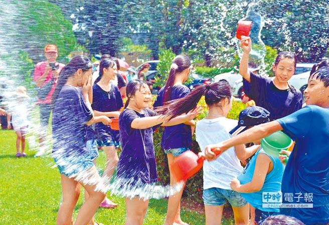 信國社區以潑水儀式來拉近與民眾間的距離。  (林和生攝)