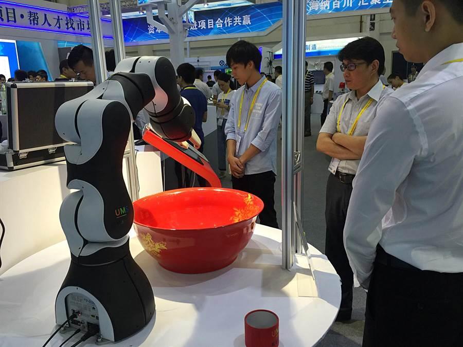 廈洽會中展示一台由協作機器人和視覺定位系統組成的互動博弈的機器人。機器人通過視覺定位,驅動機械手精確抓住骰子進行投擲,而後由視覺系統快速識別投擲點數,用語音播報出來,並能自動記錄結果。(王雅芬/攝)