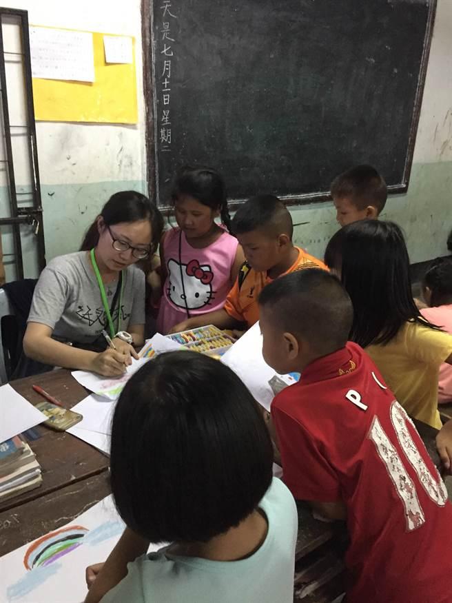 玄奘大學青年海外志工服務隊團員張婷暖正在教導低年級同學發揮創意繪畫出美麗的作品。(圖/教育部提供)