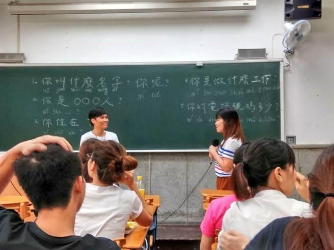 青年志工教導外籍移工練習中文會話。(圖/教育部提供)