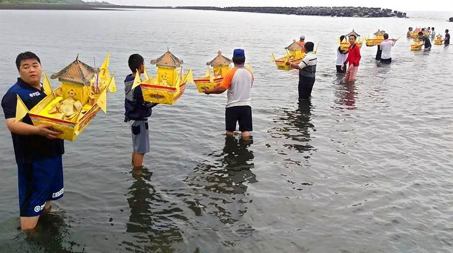 東港東隆宮舉辦普渡,工作人員將19艘水船放入海中,接引海上遇難喪命的無主孤魂,上岸接受普渡供養。(潘建志攝)