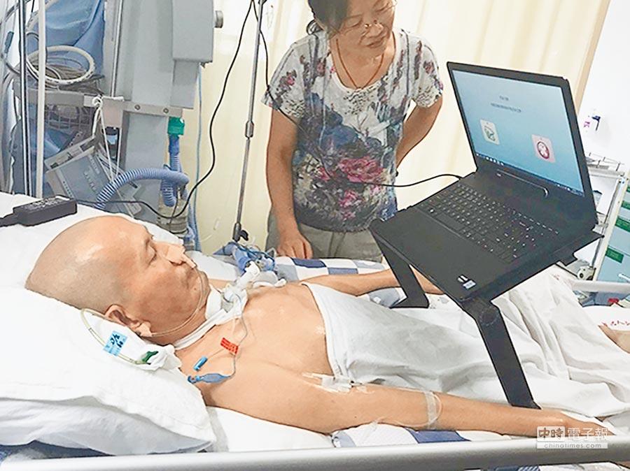唐貴安的妻子在幫他用電腦。(取自澎湃新聞網)