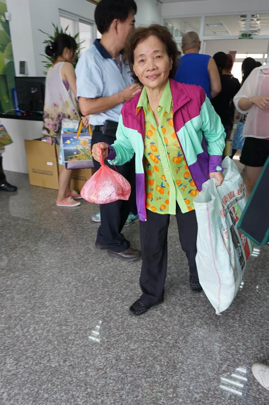70歲鄭蘭香阿嬤領取愛心月餅與生活用品,她眼泛淚光說「謝謝社會還記得我們!」。(王文吉攝)