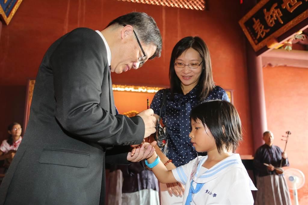 台南市代理市長李孟諺在孔廟大成殿為小一新生點硃砂、啟智慧。(台南市政府提供)