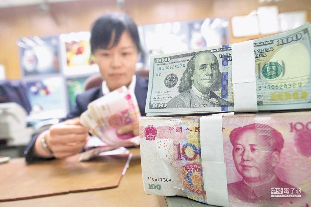 離岸人民幣兌美元5天來首上漲,未受標普下調中國評級影響。圖為山西太原銀行員工清點人民幣。(中新社)