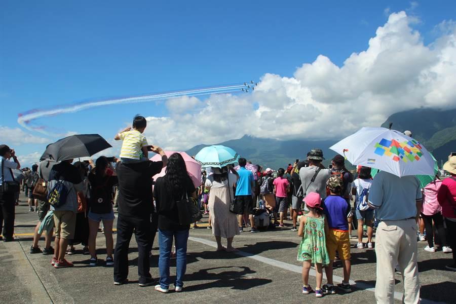花蓮空軍基地今開放民眾入營參觀,1名父親將幼兒背上肩膀,讓孩子看清雷虎小組的英姿。(張祈攝)