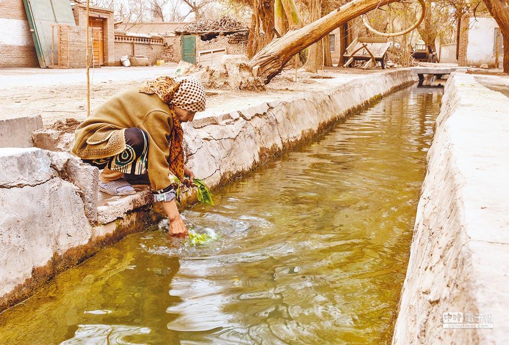 一位維吾爾族老人在用坎兒井水洗菜,準備做晚餐。(新華社資料照片)