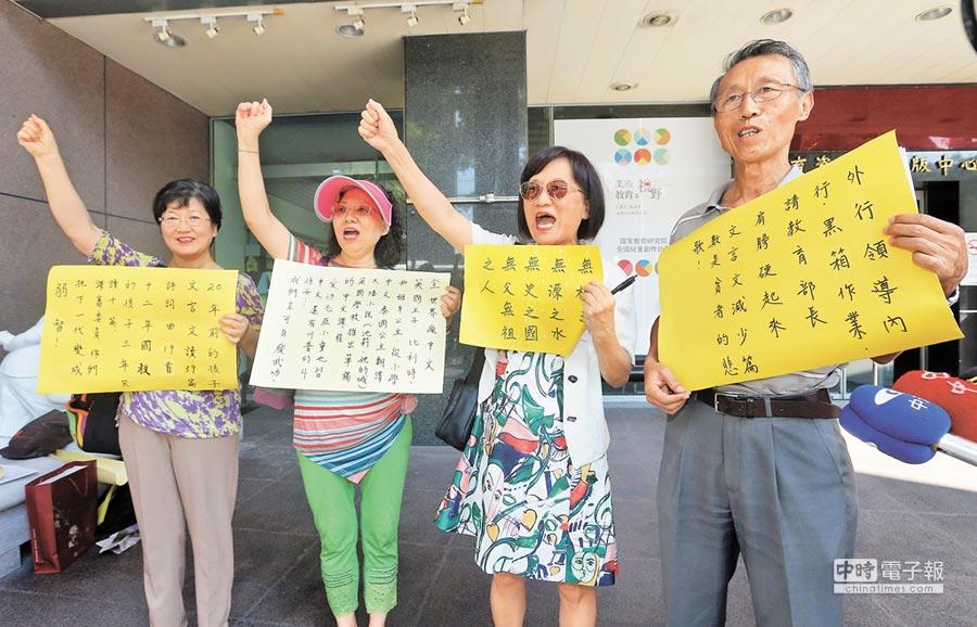 力挺文言文的中華語文教育促進協會教師,及中山女高退休教師譚家化(右二)等人,昨到課審會現場舉牌表達立場,呼籲維持文言文比率。(趙雙傑攝)