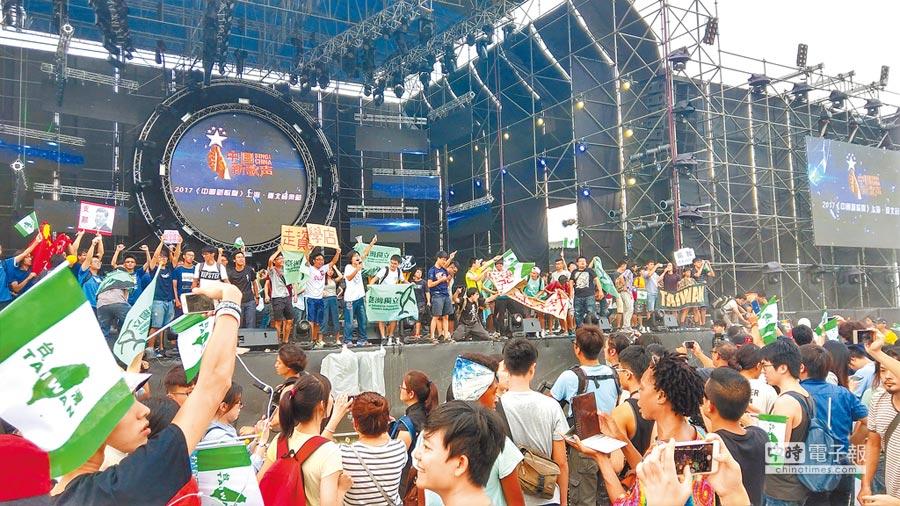 「2017『中國新歌聲』上海.台北音樂節」24日在台大田徑場舉行,闖入的抗議民眾與學生,在活動宣布提前結束後上台表達訴求。(記者潘維庭攝)