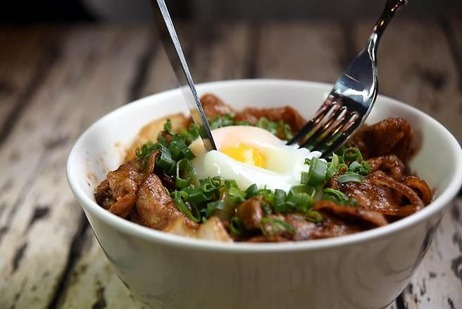 〈豚極燒肉丼飯〉有「薑汁醬燒」與「味噌醬燒」兩種口味,最上層並有一顆溫泉蛋,蛋液可增加香氣與肉片柔滑度。(圖/姚舜攝)