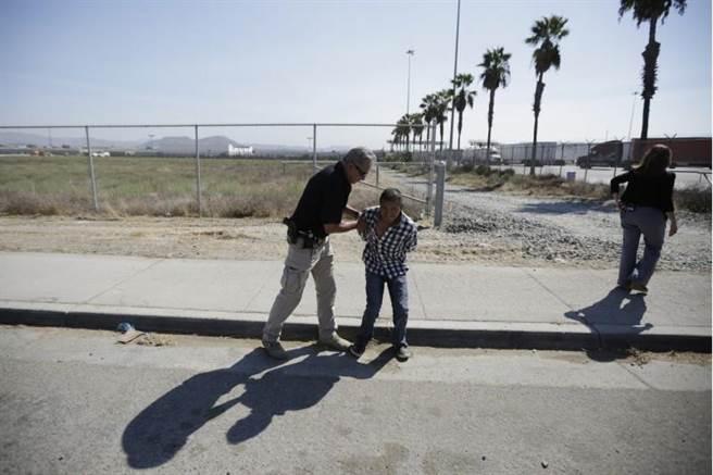 一名男子因跨越聖地牙哥和提華納之間的籬笆,遭到美國邊境巡防官員逮捕。(美聯社)