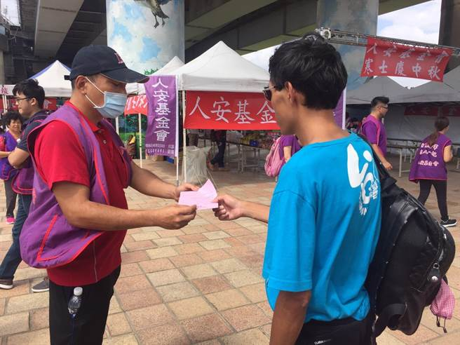 楊大哥(左)接受人安基金會扶助,參與活動幫忙發傳單。(洪安怡攝)