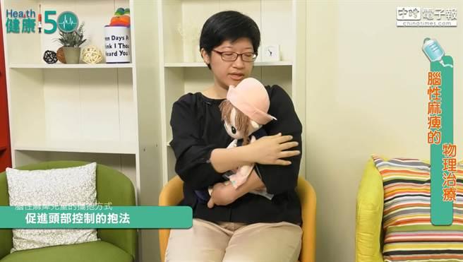 促進頭部控制的抱法: 大人以手臂固定肩膀,使孩子雙手在中間並維持頭部直立。(林勝發攝)