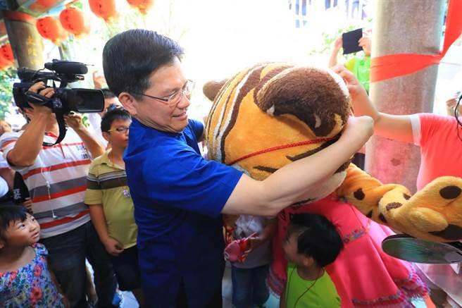 東勢區「鯉魚伯公文化祭」1日熱鬧登場,市長林佳龍替花博吉祥物樂虎「帶絭」。(陳淑娥攝)
