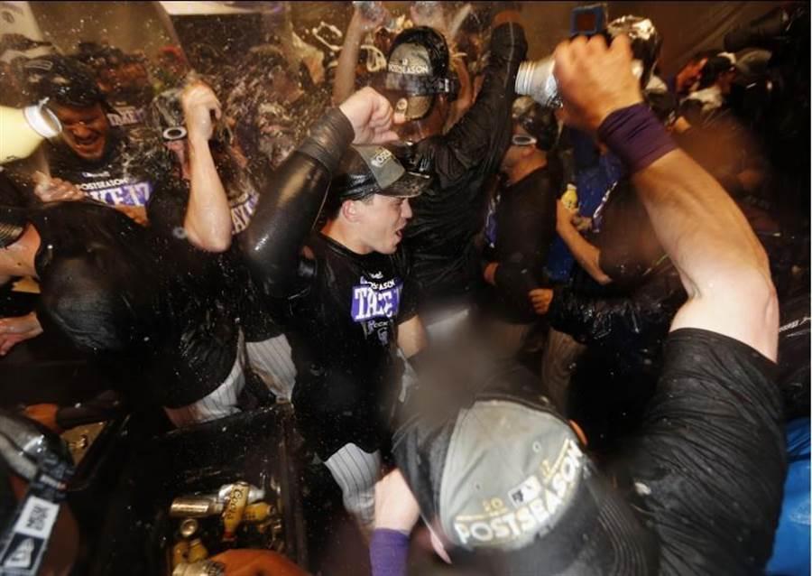 洛磯睽違9年再嘗季後賽滋味,全隊開心的大洗香檳浴。(美聯社)