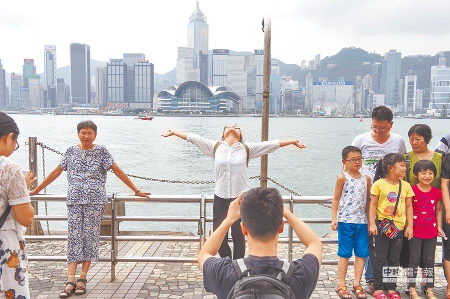 大陸超級黃金周,有一半大陸人在外旅遊。圖為大陸遊客在香港尖沙咀海邊留影。(新華社)
