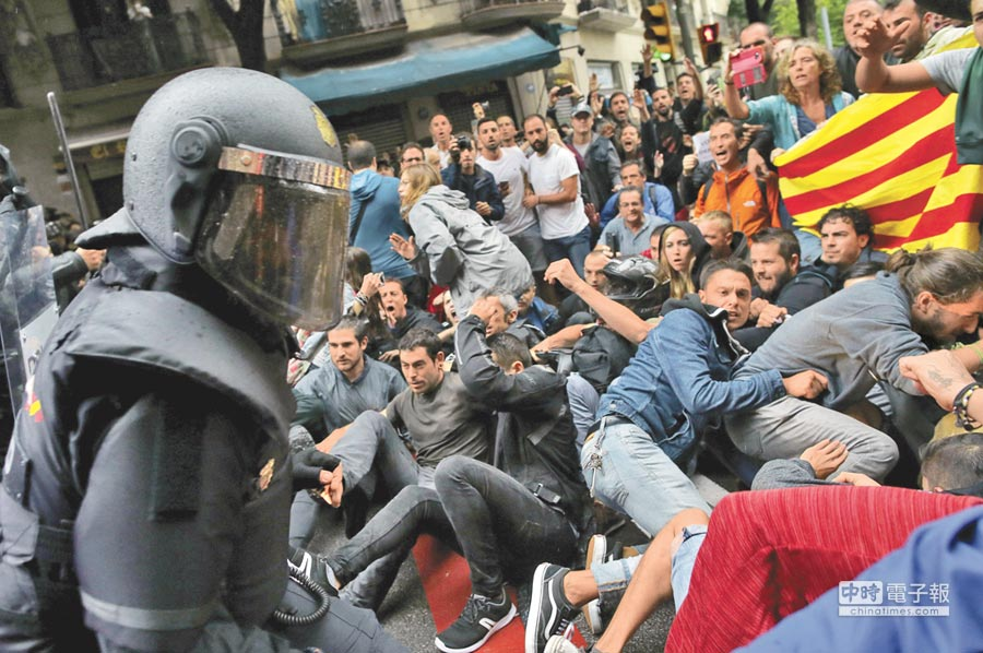 加泰隆尼亞獨立公投,1名警察手持警棍驅趕支持公投群眾。(美聯社)