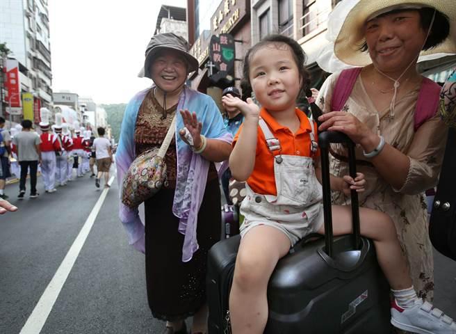 高雄臨海二路旁1位小妹妹坐在行李箱上觀看生態交通全球盛典踩街遊行。(王錦河攝)