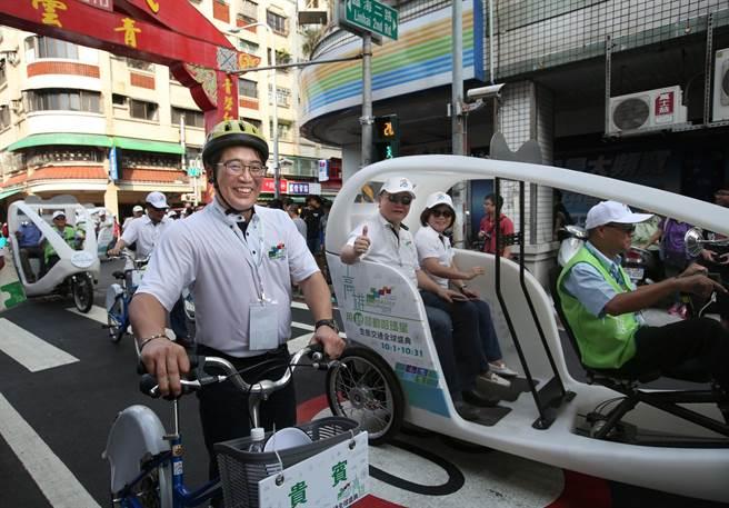 高雄民政局長張乃千(前排左)騎乘C-bike,副市長許立明(中)和許銘春(中偏右)一同搭乘Velotaxi電動三輪車參加交通全球盛典踩街遊行。(王錦河攝)