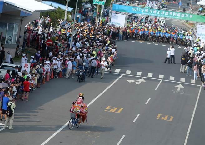 2017生態交通全球盛典嘉年華踩街遊行為盛典揭開序幕,吸引上千群眾參與,自行車隊出發前1位電音三太子人偶騎C-bike行經鼓山一路。(王錦河攝)