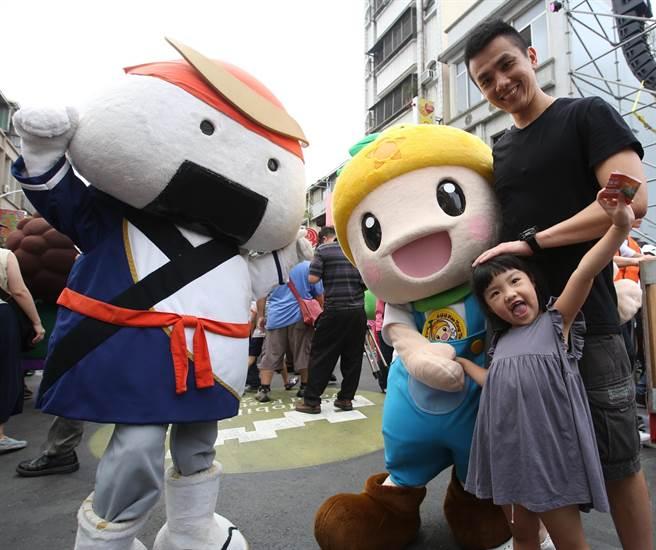 1對父女和農業局吉祥物高通通(右)及日本飯糰造型吉祥物(左)在高雄濱海一路生態交通遊行終點合影。(王錦河攝)