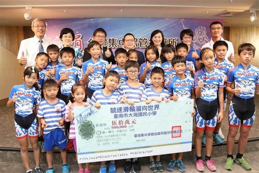 集保結算所董事長林修銘(後排中間)代表該公司捐助大灣國小滑輪溜冰隊相關訓練經費。(圖/集保結算所提供)