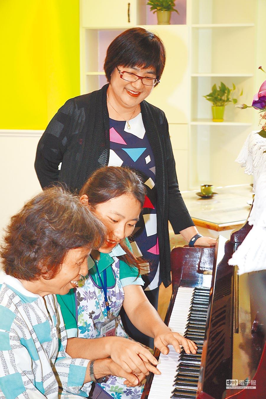板橋愛活樂園13日正式啟用,照服員引導中度失智的蔡女士彈鋼琴。(葉書宏攝)