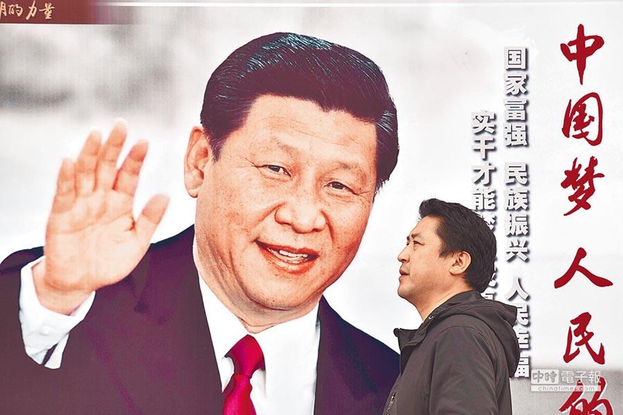 圖為一名男子走過一張以習近平的口號「中國夢,人民夢想」為標題的海報。(法新社)