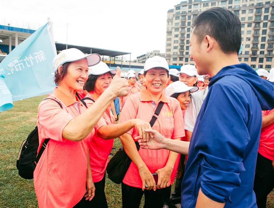 新竹市政府日前舉辦長青運動會,遭市議員抨擊在雨中彩排,還安排長輩排隊與市長握手合照。(陳育賢翻攝)